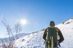 Woman backpacker trekking on snow on the Alps. Rear view, winter lifestyle, cold feeling, sun star in backlight. Royalty Free Stock Image