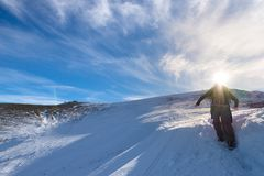 Woman backpacker trekking on snow on the Alps. Rear view, winter lifestyle, cold feeling, sun star in backlight. Stock Photography