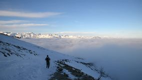Woman backpacker trekking on snow on the Alps. Rear view, winter lifestyle, cold feeling stock video