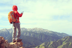 woman backpacker use digital tablet taking photo on mountain peak cliff Royalty Free Stock Photos