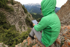 Woman backpacker use digital tablet taking photo on mountain peak cliff Stock Photography