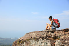 Woman backpacker use smartphone on mountain peak Stock Image