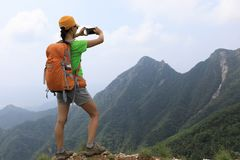Woman backpacker use smartphone on mountain Royalty Free Stock Photos