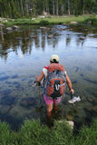 Woman backpacker wading across river Royalty Free Stock Images