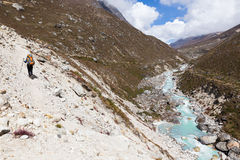 Woman backpacker walking mountain trail above river stream. Royalty Free Stock Photography
