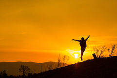 Woman backpacking to watch the sunset.Silhouette Stock Photos