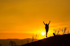 Woman backpacking to watch the sunset.Silhouette,Jumping glad.  Royalty Free Stock Photos