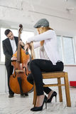 Woman backwards on chair listen contrabass play Stock Photography