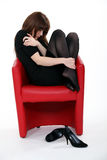 Woman after a bad day. Woman curled up in a chair after a bad day Royalty Free Stock Photos