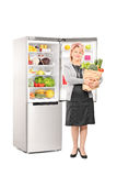 Woman with bag of groceries in front of a fridge Stock Photos