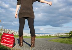 Woman with bag hitchhiking. In countryside Stock Images