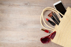 Woman bag with makeup and fashion objects on wooden table. Stock Photos