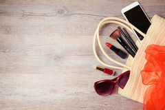 Woman bag with makeup and fashion objects on wooden table. Royalty Free Stock Image