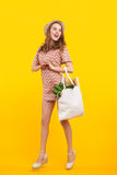 Woman with bag of vegetables. Young woman posing with bag of purchase on yellow background royalty free stock photography