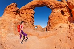 Woman with bag walks to beautiful arches Utah Royalty Free Stock Photography
