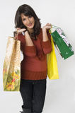 Woman with bags. Pretty young woman with green, yellow and beige shopping bags Royalty Free Stock Images