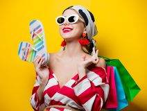 Woman with bags and flip flops. Portrait of beautiful style woman in sunglasses and striped clothes with shopping bags and flip flops shoes on yellow background stock photography