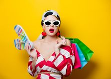 Woman with bags and flip flops. Portrait of beautiful style woman in sunglasses and striped clothes with shopping bags and flip flops shoes on yellow background stock image