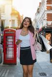 Woman with bags in her hand is shopping on a busy shopping highstreet in London Royalty Free Stock Photo