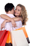 Woman with bags hugging boyfriend Stock Photos