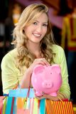 Woman with bags and a piggybank Royalty Free Stock Image