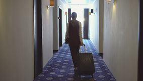 Woman with bags walks the corridor to her room stock photos