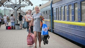 Woman with bags, woman with child go on the platform station. Train Station, Bila Tserkva, Ukraine -July 26, 2015: Young woman with shopping bags  and  woman stock footage