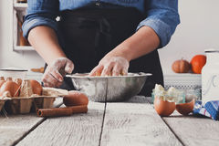 Woman baker knead yeast dough with eggs and flour. Baking concept. Unrecognizable woman knead yeast sweet dough. Female baker closeup Royalty Free Stock Images