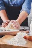 Woman baker knead yeast dough with eggs and flour Royalty Free Stock Photo