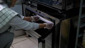 Woman baker opens the oven flaps and pulls back from the freshly baked bread, floured, which lies on a metal tray. Bakery woman opens misted leaf modern metal stock footage