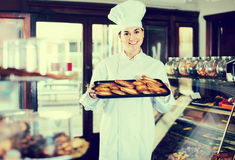 Woman baker showing warm tasty croissants Stock Images