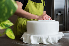 woman in bakery decorating wedding cake with white fondant stock photography