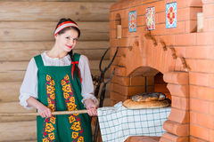 Woman bakes bread in a Russian stove Stock Photography