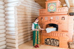 Woman bakes bread in a Russian stove Royalty Free Stock Photo