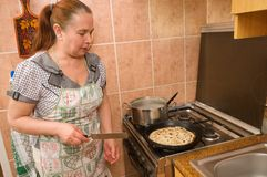 The woman bakes pancakes. Stock Photography