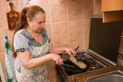 The woman bakes pancakes. Stock Photo