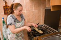The woman bakes pancakes. Stock Photo