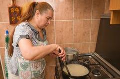 The woman bakes pancakes. Royalty Free Stock Photo
