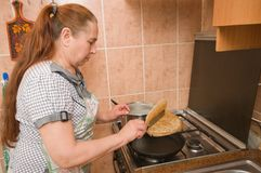 The woman bakes pancakes. Royalty Free Stock Photography