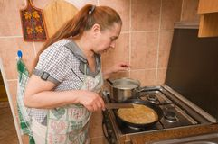 The woman bakes pancakes. Stock Image