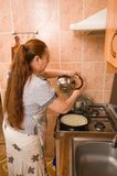 The woman bakes pancakes. Stock Images
