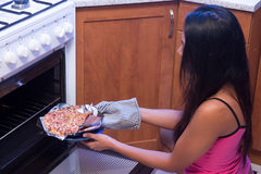 Woman bakes pizza Royalty Free Stock Photos