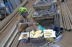 Woman baking bananas along the street and selling them. Royalty Free Stock Image