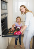 Woman baking cookies with daughter Stock Images