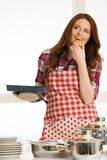 Woman baking cookies in the kitchen. Holding a plate in her hands Royalty Free Stock Images