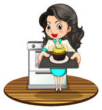 A woman baking a cupcake Stock Image
