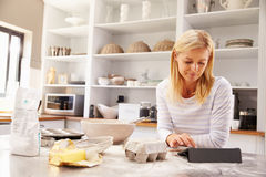 Woman baking at home following recipe on a tablet Stock Images