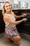 Woman baking homemade pizza. Cheerful smiling  blonde girl baking homemade pizza in the oven Stock Photo