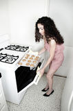 Woman Baking in Kitchen. Beautiful woman baking cakes and cookies in a white home kitchen oven Royalty Free Stock Photos