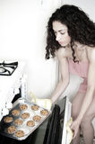 Woman Baking in Kitchen. Beautiful woman baking cakes and cookies in a white home kitchen oven Royalty Free Stock Photography